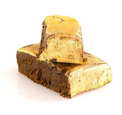Due pezzi di CBD hashish legale ricoperti da una patina d'oro